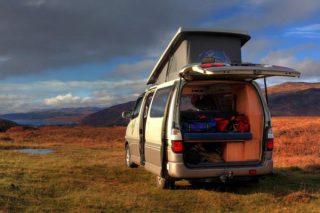 furgoneta camperizada con techo elevado y preparada para acampar