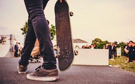 imagen de persona caminando con un skate en la mano